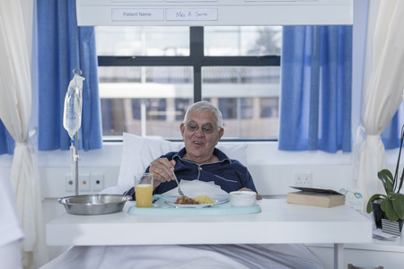Senior patient in hospital bed having lunch
