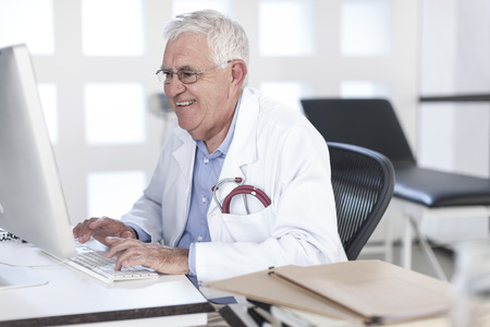 Smiling senior doctor sitting at desk working on computer