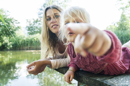 Girl lying with mother on jetty at a lake pointing finger