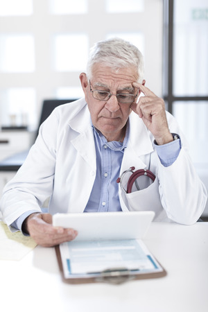 Serious senior doctor at desk looking at patient file LANG_EVOIMAGES