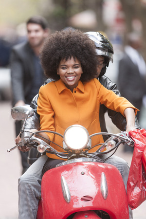 Portrait of smiling woman sitting on a motor scooter with co-driver LANG_EVOIMAGES