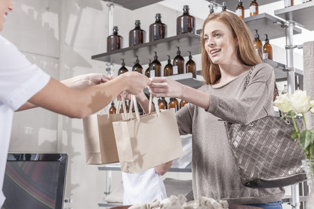 selling service: Shop assistant in wellness shop handing over bags to client LANG_EVOIMAGES