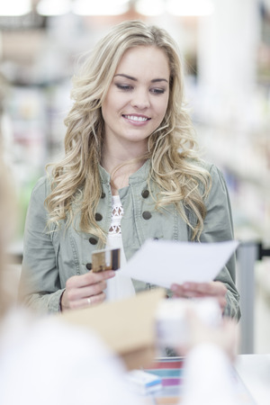 Woman at till picking up prescription, paying with credit card