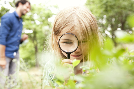 Girl in the nature looking through magnifying glass