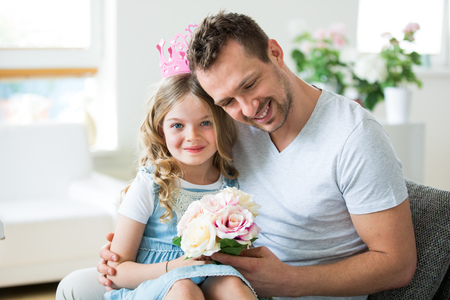 Girl wearing pink crown sitting on fathers lap with bunch of flowers