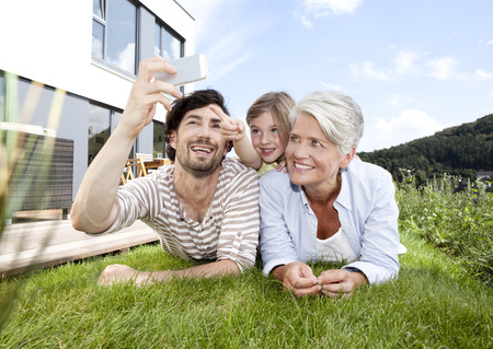 Happy grandmother, father and girl lying on lawn using cell phone