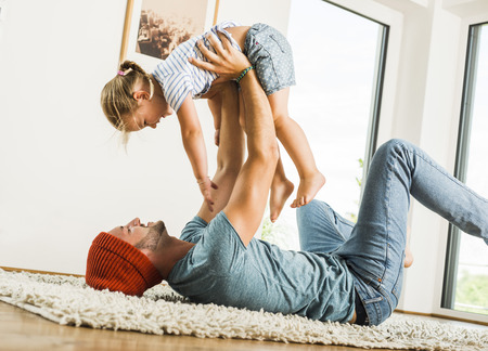 romp: Father lying in rug lifting up happy daughter LANG_EVOIMAGES