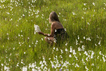 cowering: Woman crouching on a meadow picking flowers