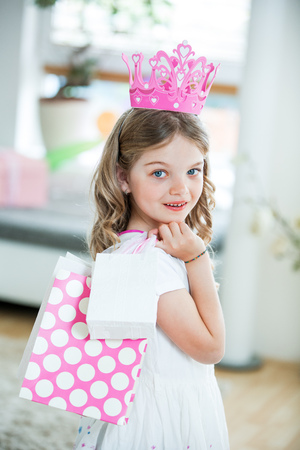 Girl wearing pink crown carrying gift bags
