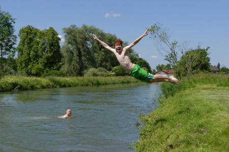 ardor: Germany, Bavaria, teenage boy jumping into River Loisach