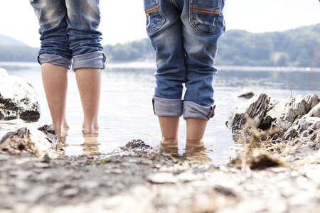 Close-up of two children standing at lakeshore LANG_EVOIMAGES