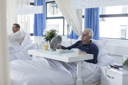 Senior patient in hospital bed looking at meal LANG_EVOIMAGES