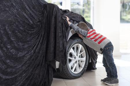 Boy at car dealer peeking at new car