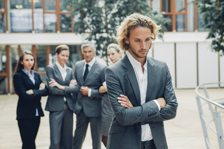 Businessman with crossed arms, excluded from group of business people