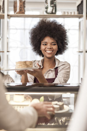 selling service: Young woman serving cake at cake counter in coffee shop