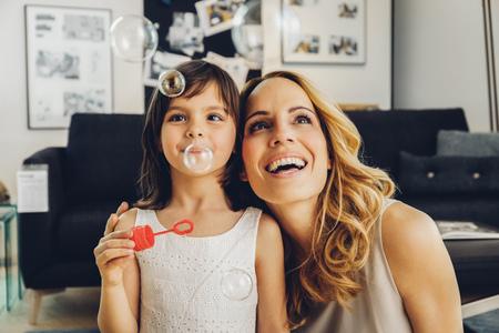 Feliz madre con hija en casa soplando pompas de jabón LANG_EVOIMAGES