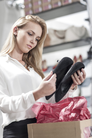 selling service: Shop assistant in shoe shop looking at shoes LANG_EVOIMAGES