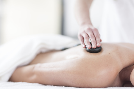Woman receiving hot stone massage in a spa LANG_EVOIMAGES