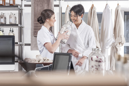 selling service: Client in bathrobe and shop assistant talking in wellness shop