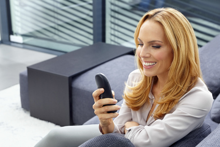 Portrait of smiling young woman sitting on couch dialing a number on cordless phone