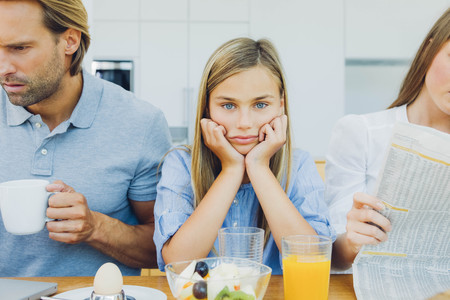 careless: Frustrated girl with distracted parents at breakfast table LANG_EVOIMAGES