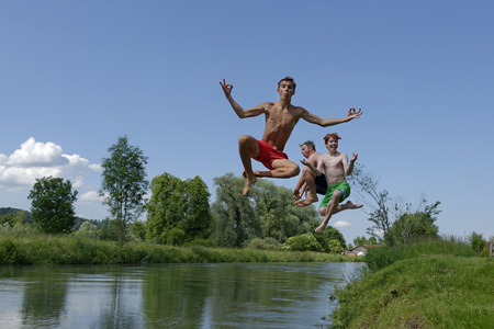 ardor: Germany, Bavaria, two teenage boys and man jumping into River Loisach