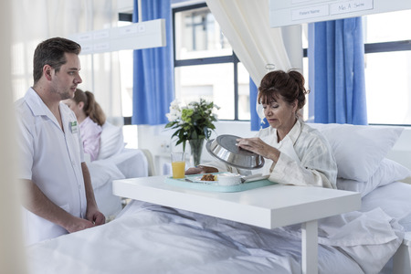 Nurse looking at skeptical patient receiving lunch