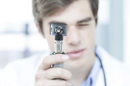 nose close up: Doctor looking through otoscope LANG_EVOIMAGES
