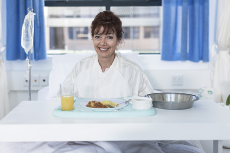 Smiling patient in hospital bed having lunch