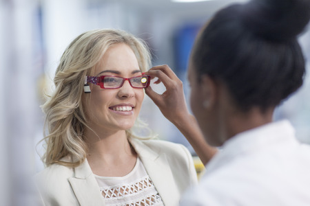 Pharmacist helps customer choosing new reading glasses