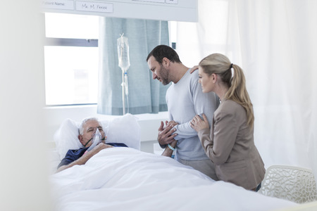 critical care: Couple visiting senior patient in hospital LANG_EVOIMAGES