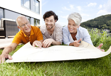 Adult son and parents lying on lawn looking at construction plan