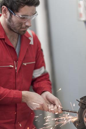 Car mechanic at work in repair garage, grinding machine
