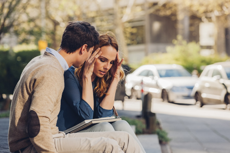 lovers quarrel: Couple sitting outdoors with woman holding head in hands