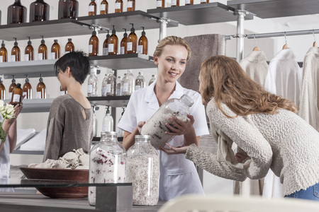 selling service: Shop assistant advising client in wellness shop
