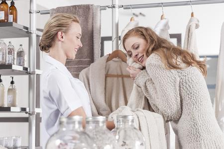 selling service: Client enjoying fluffy bathrobe in wellness shop