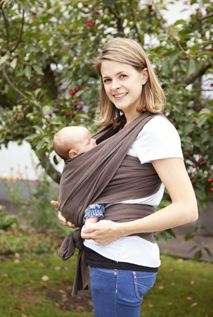 Portrait of young woman carrying baby girl in baby sling