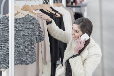 coathangers: Woman on cell phone shopping for clothes