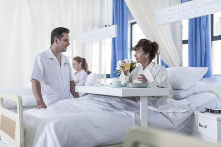 Nurse looking at patient drinking juice