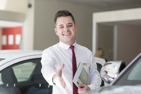 selling service: Smiling car dealer in showroom reaching out his hand LANG_EVOIMAGES