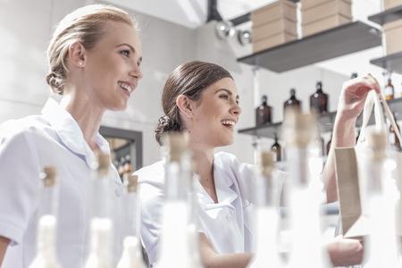 selling service: Smiling shop assistants in wellness shop handing over bag