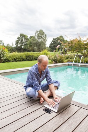 feet naked: Man sitting on floor beside a pool using laptop