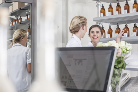 selling service: Two smiling shop assistants in wellness shop