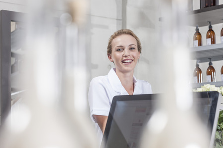 selling service: Smiling shop assistant in wellness shop