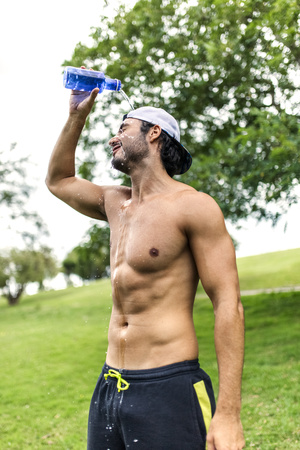 Athletic young man refreshing after training in the park