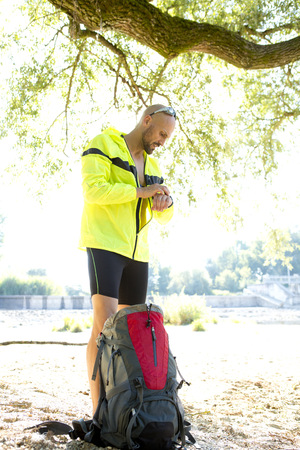 self testing: Man in sports wear with back pack adjusting his smartwatch