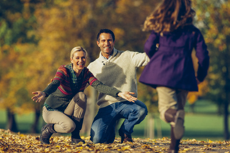Daughter running to her parents in a park on a sunny autumn day LANG_EVOIMAGES