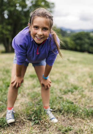 likeable: Portrait of girl standing on a meadow looking at viewer LANG_EVOIMAGES