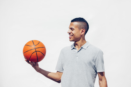 Portrait of young man with shaved hair holding basketball in front of white background LANG_EVOIMAGES
