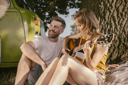 Pareja haciendo música en el árbol al lado de la furgoneta LANG_EVOIMAGES